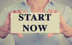 Businesswoman hands holding card sign with start now message Royalty Free Stock Image