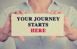 Businesswoman hands holding card sign with Your Journey Starts Here message. Closeup businesswoman hands holding white card sign with Your Journey Starts Here Stock Photography