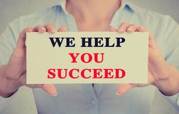 Businesswoman hands holding sign we help you succeed Stock Photos