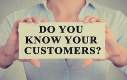 Businesswoman hands holding sign with message do you know your customers