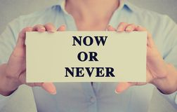 Businesswoman hands holding sign with now or never message Stock Images