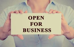 Businesswoman hands holding white sign with message open for business Stock Photo