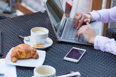 Businesswoman hands with laptop and mobile phone during breakfast. Royalty Free Stock Photography