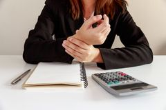 Businesswoman hands pain on desk office syndrome with notebook a Royalty Free Stock Photo