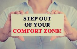 Businesswoman hands sign with step out of your comfort zone message. Businesswoman hands holding white card sign with step out of your comfort zone text message stock images