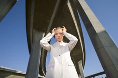 Businesswoman with hands to head beneath overpasses, portrait, low angle view Royalty Free Stock Photo