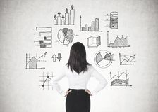 Businesswoman with hands on waist, data graphs stock photography