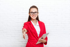 Businesswoman handshake, hold hand welcome gesture wear red jacket glasses Royalty Free Stock Images
