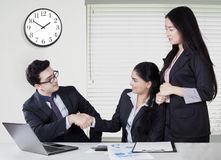 Businesswoman handshakes with her partner. Portrait of successful businesswoman closing a meeting and shaking hands with her partner in the office stock image
