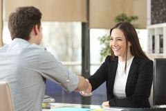 Businesswoman handshaking with client closing deal. Happy businesswoman handshaking with client closing deal in an office interior with a window in the Royalty Free Stock Photography