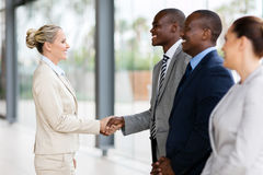 Businesswoman handshaking employees. Middle aged businesswoman handshaking with group of employees in office stock photo
