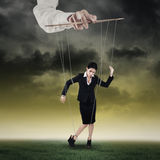 Businesswoman hanging on string 1. Businesswoman hanging on string and controlled by a hand stock photography