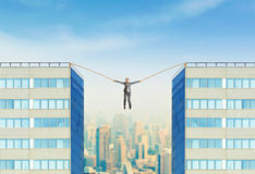 Businesswoman hanging between two skyscrapers Royalty Free Stock Photos