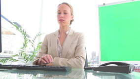 Businesswoman hanging up a phone. In an office stock video