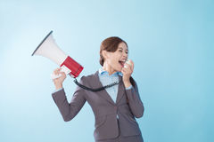 Businesswoman happy with a megaphone. Business woman happy with a megaphone isolated on blue background, model is a asian beauty Royalty Free Stock Photo