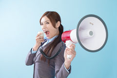 Businesswoman happy with a megaphone. Business woman happy with a megaphone isolated on blue background, model is a asian beauty Stock Images