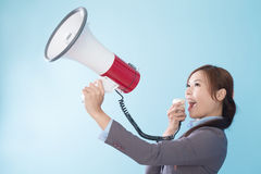 Businesswoman happy with a megaphone. Business woman happy with a megaphone isolated on blue background, model is a asian beauty Stock Photography