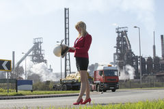 Businesswoman with hard hat outside steelworks Royalty Free Stock Photos