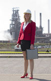 Businesswoman with hard hat outside steelworks Royalty Free Stock Photography