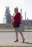 Businesswoman with hard hat outside steelworks Stock Photography