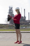 Businesswoman with hard hat outside steelworks Stock Photo