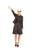 Businesswoman in hard hat pointing up. Royalty Free Stock Photo
