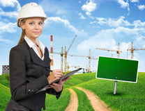 Businesswoman in hard hat, writing on clipboard Stock Photography