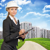 Businesswoman in hard hat, writing on clipboard Royalty Free Stock Photos