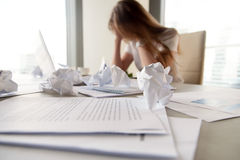 Businesswoman has no idea what to do with problem. Businesswoman sitting with head in hands at desk covered crumpled papers. Office worker tired of too much Royalty Free Stock Photography
