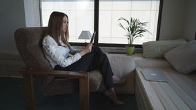 A businesswoman has an online conversation sitting on the armchair stock footage