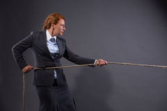 Businesswoman hauling at a rope. Conceptual image. Businesswoman pulling on a strong rope isolated on dark grey. Lady is not afrait of existing problems Stock Image