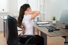 Businesswoman Having Backpain In Office. Young Businesswoman Sitting On Chair Having Backpain In Office Royalty Free Stock Photography