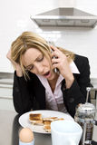 Businesswoman having breakfast in the kitchen and talking on the phone Royalty Free Stock Photography