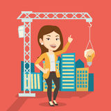 Businesswoman having business idea. Young caucasian woman pointing at idea light bulb hanging on crane. Architect having idea in town planning. Concept of new Royalty Free Stock Image