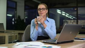 Businesswoman having coffee break on night shift in office, avoiding unloved job. Stock footage stock video