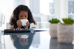 Businesswoman having coffee while sitting at desk Stock Photos