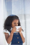 Businesswoman having coffee while standing by window Stock Photography