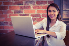Businesswoman having coffee and working on laptop Royalty Free Stock Image