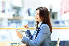Businesswoman having a cup of coffee while reading Stock Photos