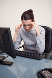 Businesswoman having a headache at her desk Royalty Free Stock Photography