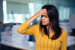 Businesswoman having headache in office Royalty Free Stock Photos