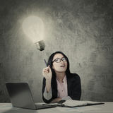 Businesswoman having an idea with a bright bulb Royalty Free Stock Image