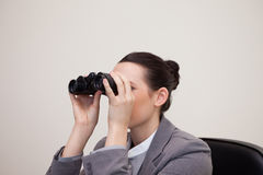 Businesswoman having a look through binoculars Stock Images