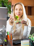 Businesswoman having lunch in office Stock Photo