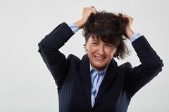 Businesswoman having a nervous breakdown. Mature businesswoman having a nervous breakdown, isolated on gray background stock images