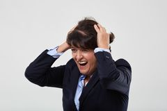 Businesswoman having a nervous breakdown. Mature businesswoman having a nervous breakdown, isolated on gray background stock image