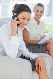 Businesswoman having a phone call while her colleague writing Stock Image
