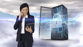 Businesswoman having phone call and holding tablet computer in front of server tower