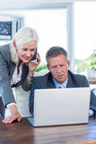 Businesswoman having phone call and looking at laptop with her colleagues Royalty Free Stock Photo