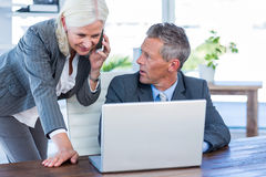 Businesswoman having phone call and looking at laptop Stock Photo